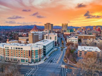 an aerial view of Asheville at sunset. The sky is orange and yellow. You can see buildings, streets, and the mountains in the distance on your weekend in Asheville.