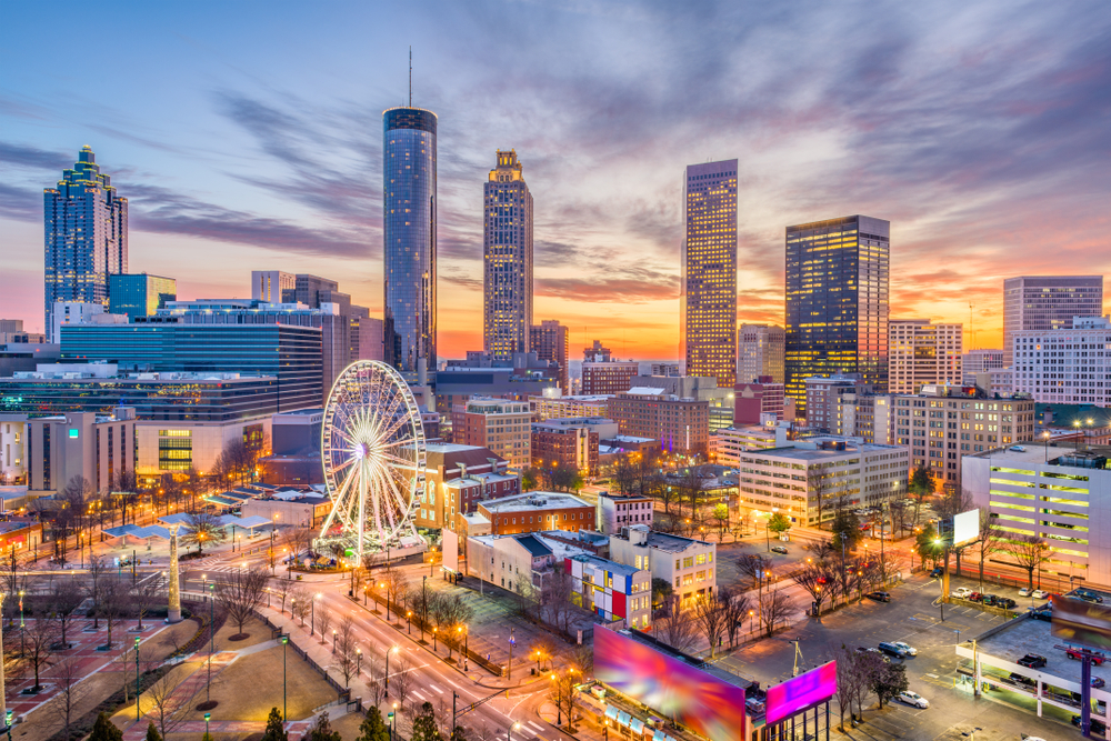 An aerial view of Atlanta's skyline. You can see large towers, a Ferris wheel, and some smaller buildings. The buildings are all lit up and it is twilight. It is one of the best things to do in Georgia.