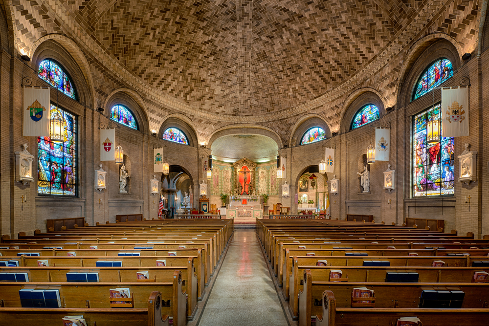 The inside of the Basilica of Saint Lawrence. The ceiling is herringbone laid brick, there are large stained glass windows on either side of the building, and at the end there is an elaborate alter. There are rows of wooden pews with bibles and hymnals in them.