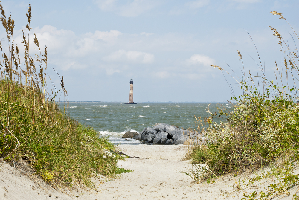sandy path leading to water with a lighthouse in the distance