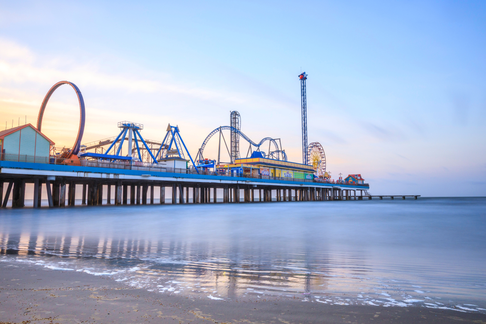Galveston pier over the water with roller coasters and ferris wheel on it