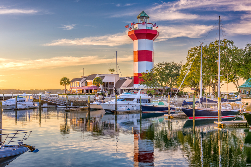 marina, boats on the water, and a red and white striped lighthouse