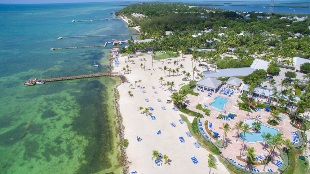 aerial photo of white sand, water, and resorts with swimming pool