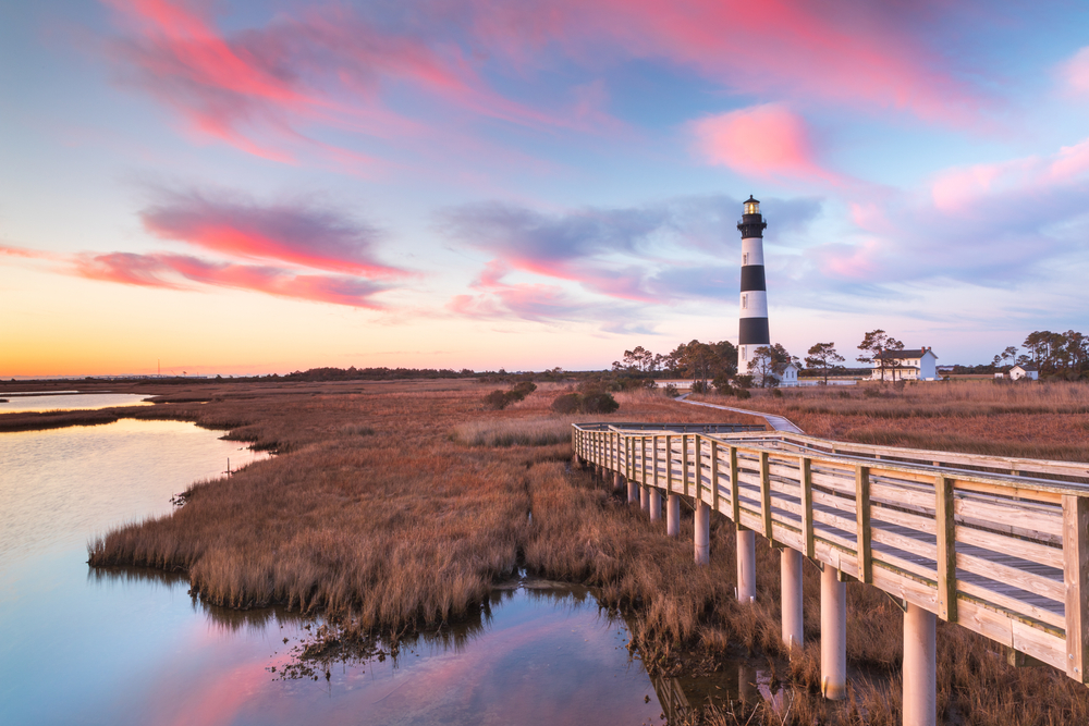 beautiful sunset over wooden boardwalk, water, and lighthouse