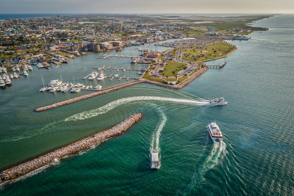 aerial photo of bay and ocean with boats driving through the water
