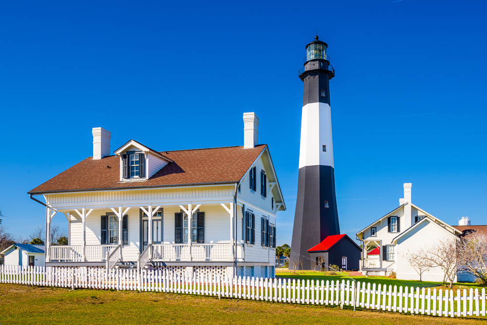 black and white striped lighthouse next to white building on a sunny day