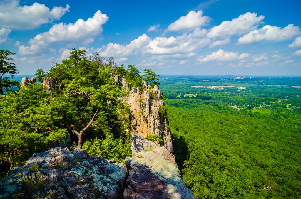 The peak of Crowders Mountain, one of the best things to do in North Carolina, casts a shadow on the lush forest below.