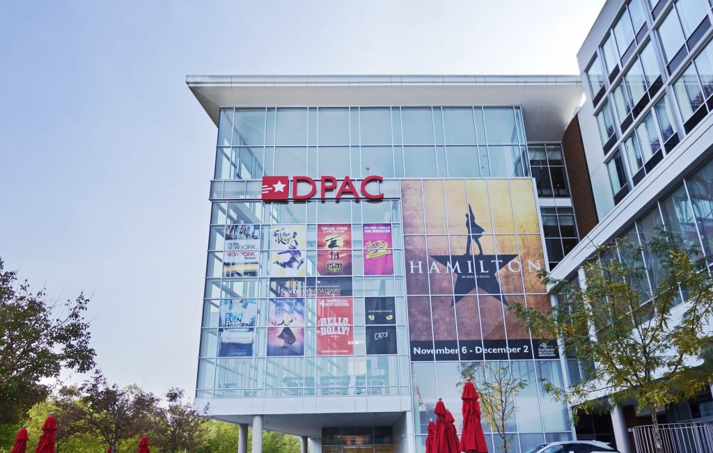The exterior of the Durham Performing Arts Center, one of the best things to do in North Carolina, displays posters of Broadway shows coming to town.