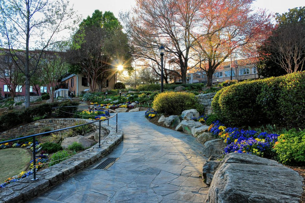 A stone pathway lined with rocks and beautiful flowers winds through Falls Park, one of the best things to do in North Carolina