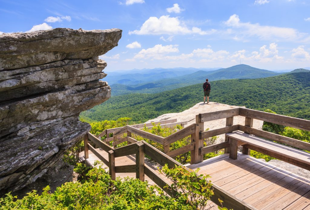 A hiker looks down at the forest below at the summit of Grandfather Mountain