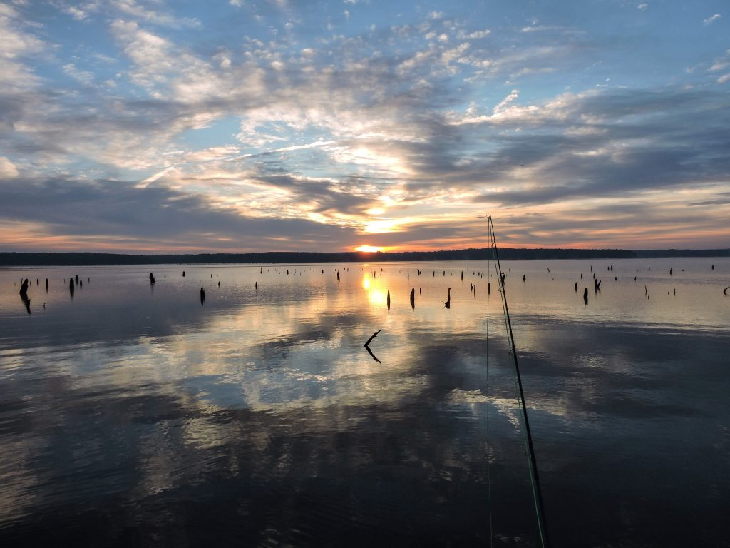 A fishing line is cast over Jordan Lake as the sun sets over the water.