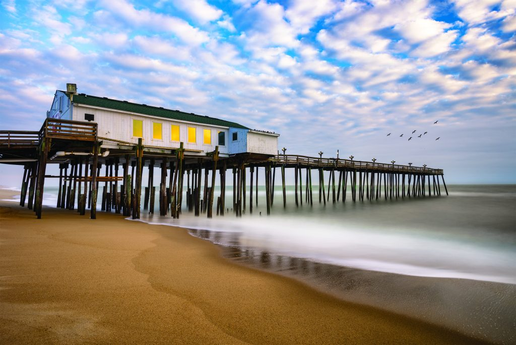 The pier at Kitty Hawk on the Outer Banks stand over misty waves washing up on shore.