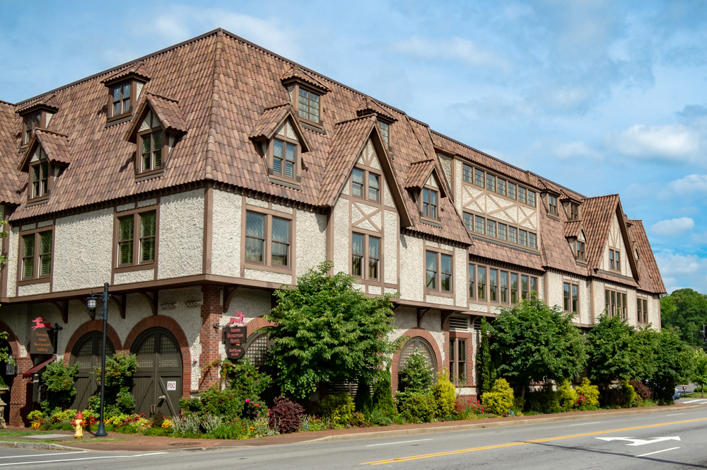 The exterior of a set of buildings at the Biltmore Village. The buildings are styled like old European cottages with the tile on the roof supposed to look like a thatched roof. It is a cream color with brown trim around the doors and windows. In front of it there is a garden that wraps around its exterior where there are shrubs and plants with red flowers.