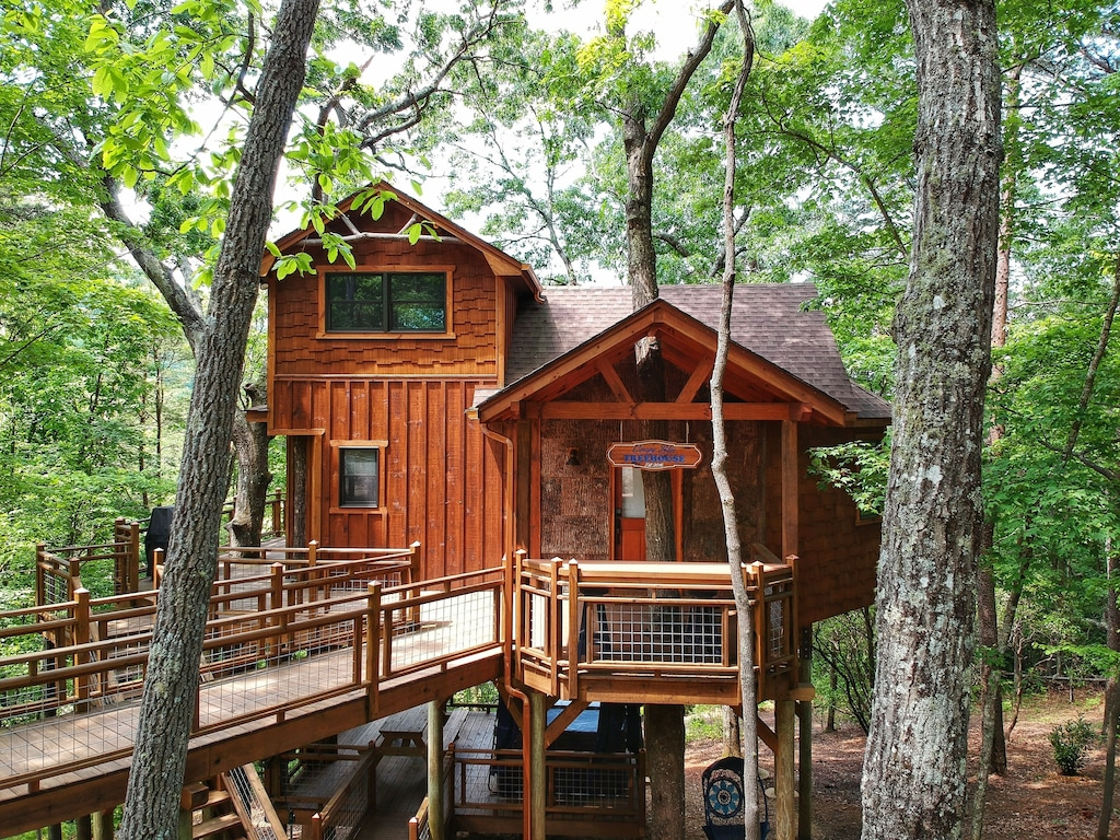 A wooden treehouse on a platform in the woods. It has a ramp leading to a large porch that wraps around the treehouse. You can see trees coming through the deck and the house.