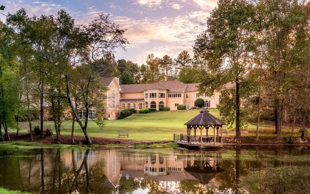 The view of the Château Élan Winery & Resort. It is a large classic style building that is kind of peach in color. In front of it there is a large pond with green algae, trees around it, and a gazebo on the shore.