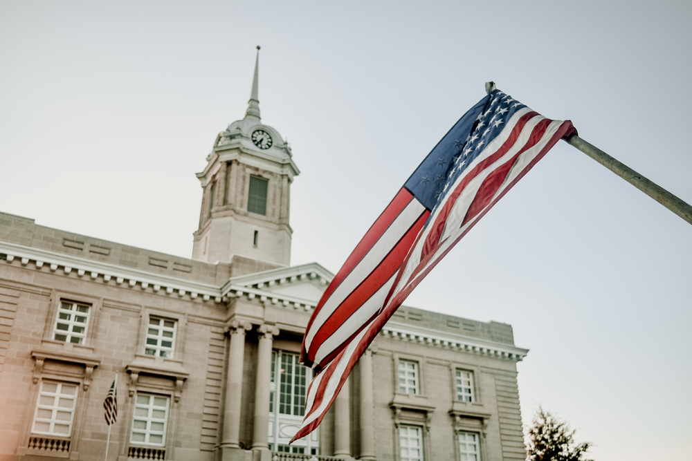 Looking up at a stone government building. It is a classic Greek Revival style building. There is a large American flag hanging in front of the building. One of the cutest small towns in Tennessee.