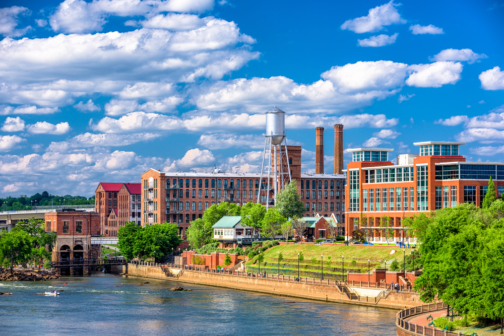 A view of the Columbus skyline from the water. There are old and new brick buildings, a walkway along the water, and a silver metal water tower. There are lots of fluffy clouds in the sky and it's very sunny.
