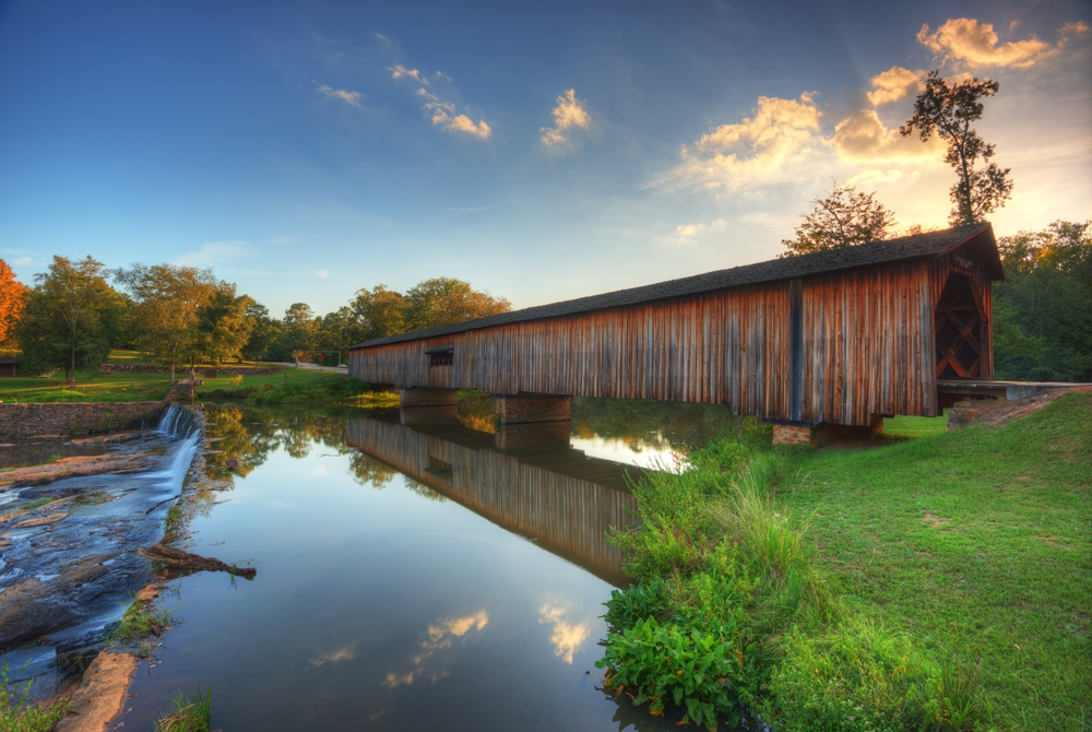 A long wooden covered bridge. It connects two pieces of grassy land across a river. The river has a small manmade waterfall not far from the covered bridge.