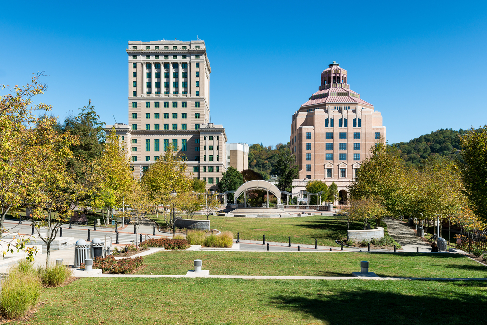 A view of downtown Asheville, one of the best places to see during a weekend in Asheville. There is a large green space, sidewalks, and old large buildings.