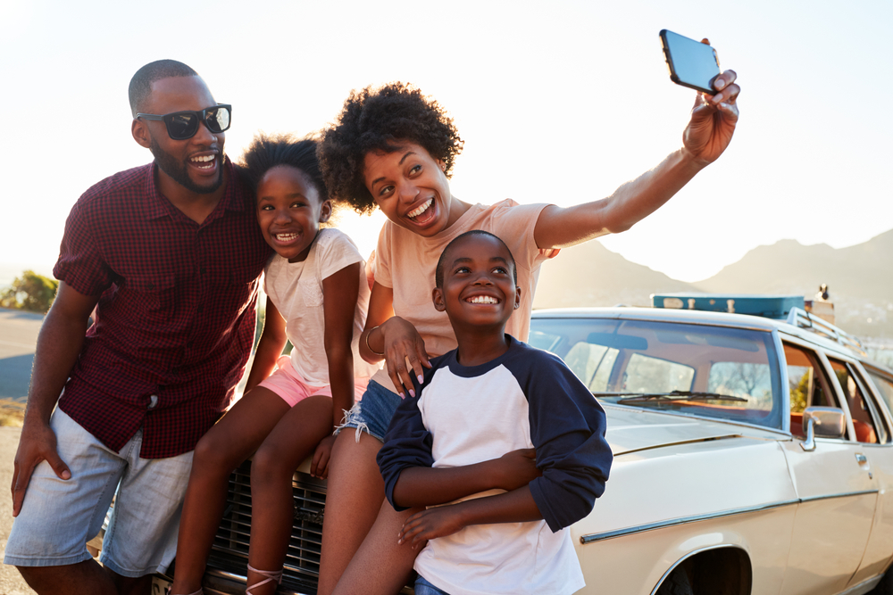 A family consisting of a man, woman, and a son and daughter. They are sitting on the hood of their car and the mom is taking a selfie. You can see luggage strapped to the top of their car.