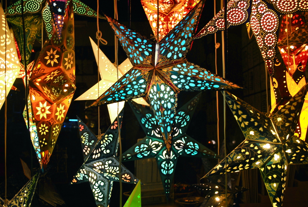 Hanging paper star lanterns in all types of colors and patterns. They are hanging from the ceiling in a dark room and are lit up from inside.
