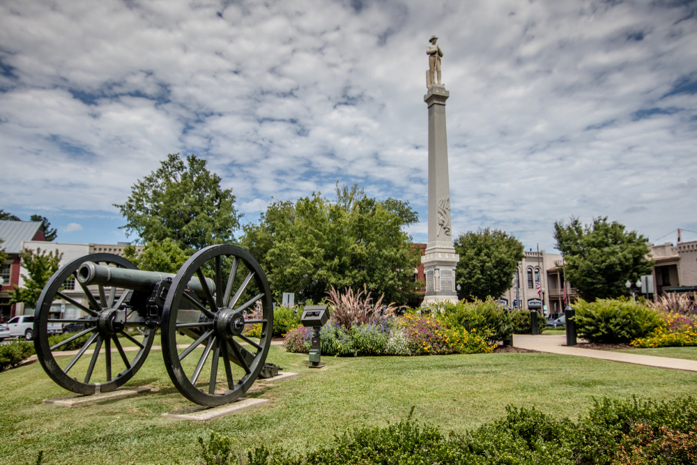 A Civil War monument in the middle of the town square of Franklin. There is a grassy area around the monument and flowers and shrubs with yellow, pink, and purple flowers. There is also an old cannon in the grassy area.