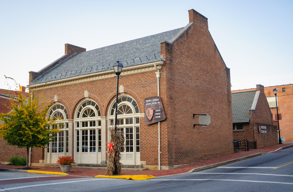 The exterior of the Andrew Johnson Historic Site. It is a brick building with tall windows on the front that arch. It is on the corner of a street and there is a smaller brick building behind it.