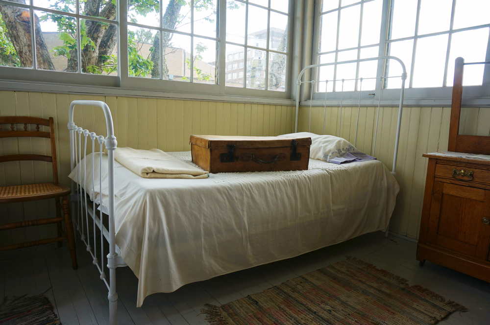 A room that looks old. There is an antique iron bed with cream sheets and an old leather suitcase is on top of it. In the room you can also see a chair, a dresser, and a rug. The walls are painted pale yellow half way up and then there are windows.