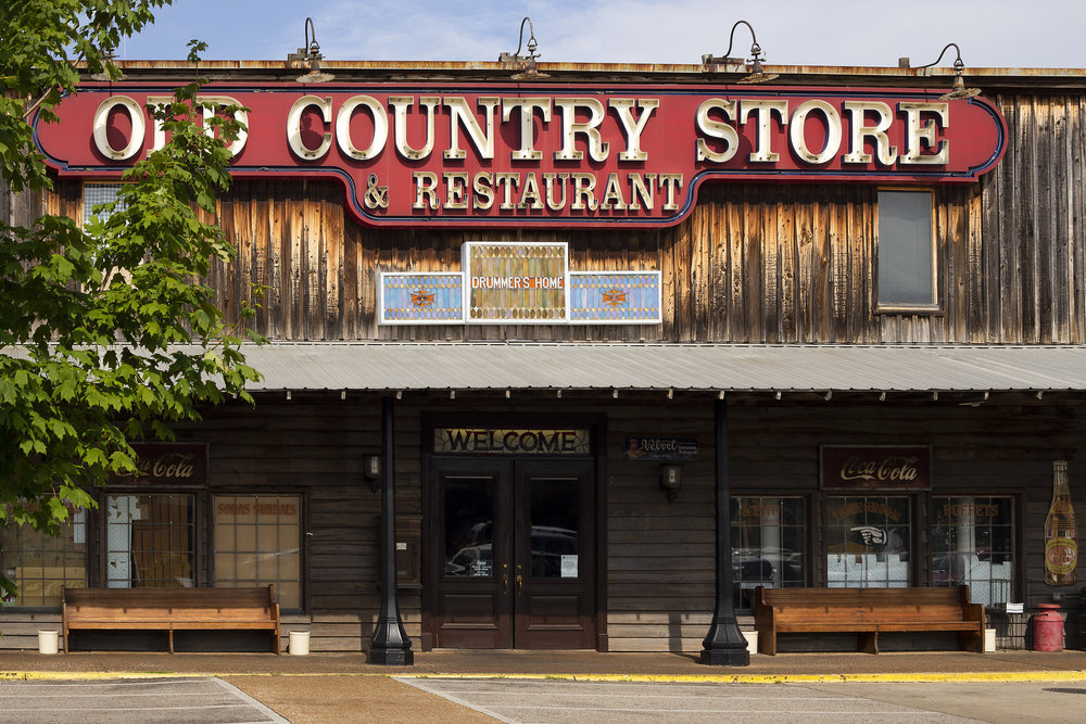 The front exterior of an old wood building with a red sign that says 'Old Country Store and Restaurant'. There are benches under an awning next to the front door.
