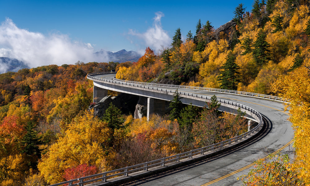 The Linn Cove Viaduct, a stretch of road on the Blue Ridge Parkway that is curving around a mountain. The road is surrounded by trees with green, yellow, orange, and red leaves. In the distance you can see low clouds and mountains. It is a must see during a weekend in Asheville.