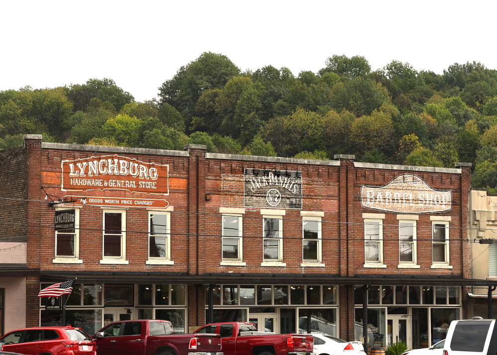 A row of old brick buildings with painted signs on them. They say 'Lynchburg Hardware and General Store', 'Jack Daniels', and 'Barrel Shop'. There are tall windows on the second floor and shop windows on the bottom of the buildings. There are red and white cars parked in front of it.