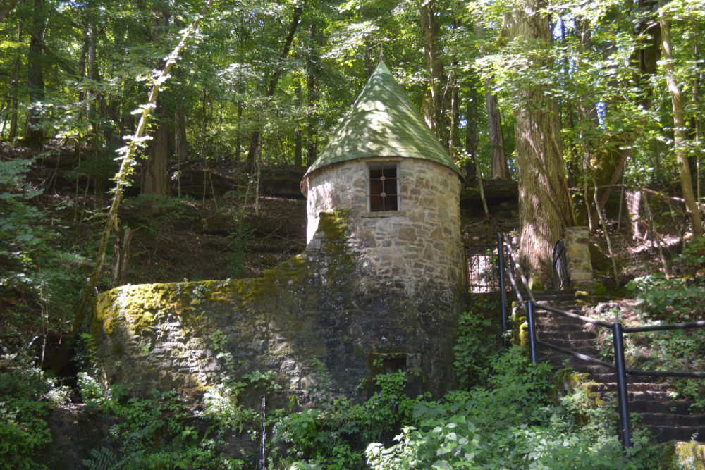 An old stone turret and wall surrounded by a dense forest. There are stairs leading up a hill with a black metal railing next to them. The stone building and wall has ivy and moss growing on it.