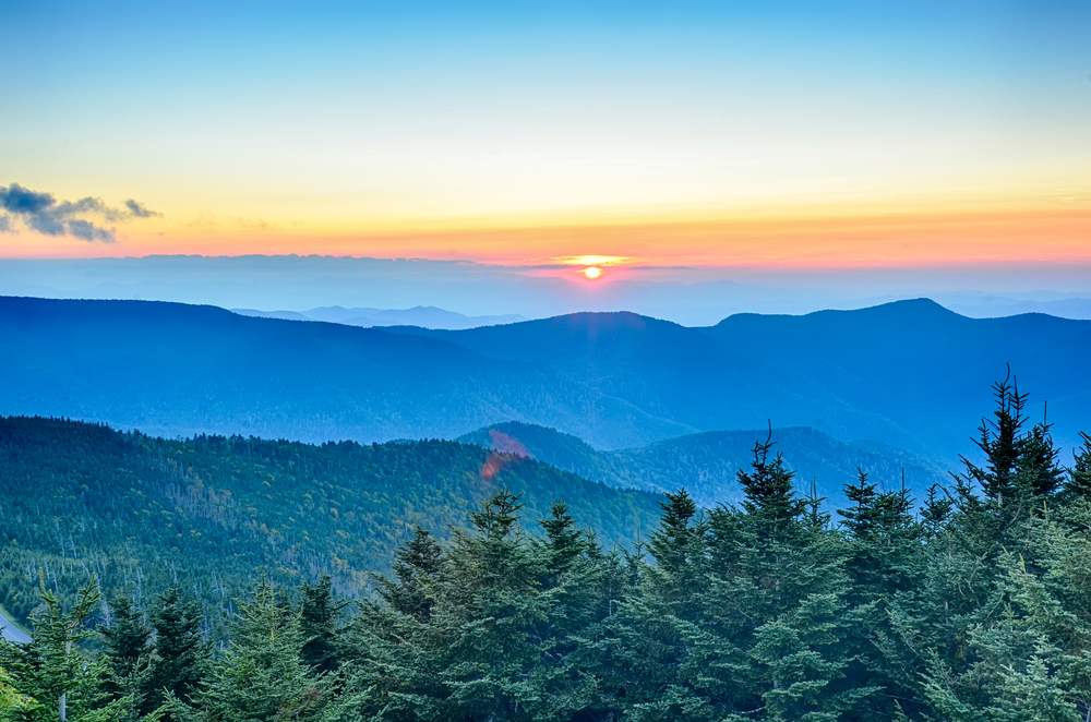 The view looking out at the Blue Ridge Mountains from the peak of Mount Mitchell. You can see mountain peaks in the distance and the sun is setting behind them. The mountains seem to be blue and are covered in trees.