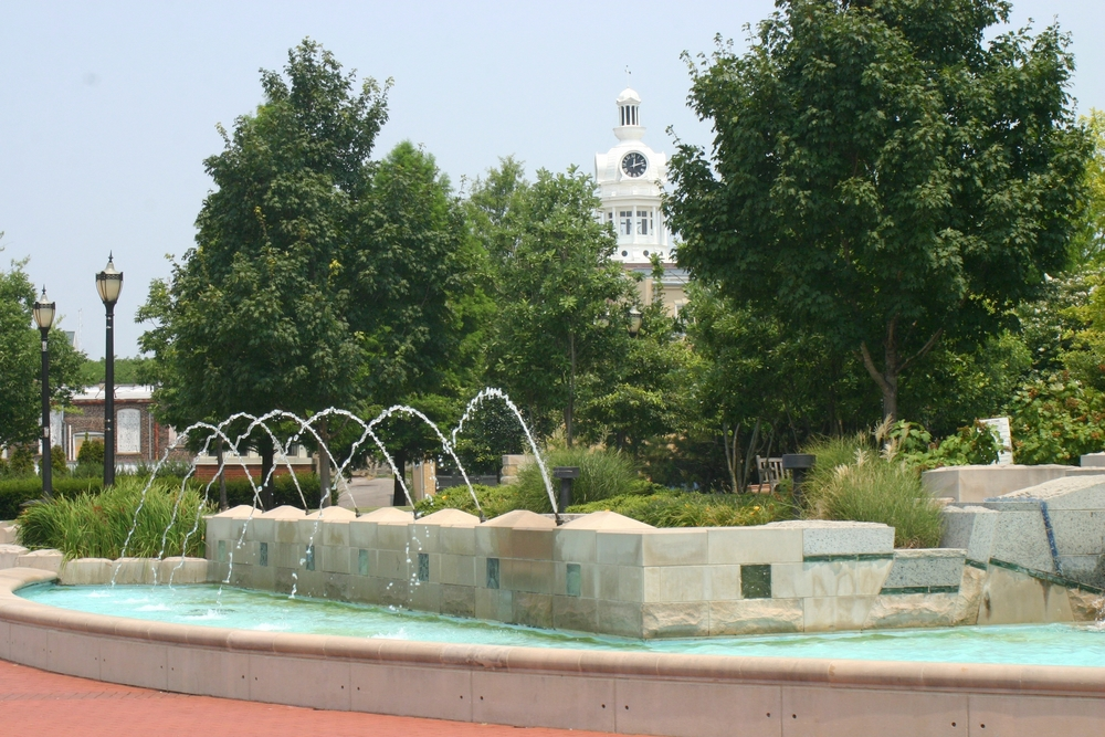 A fountain in the town square of Murfreesboro. The fountain is stone and there is water shooting out if it. Around the square there are shrubs, grasses, and green trees. There are also some light posts and you can see a government building behind the trees.