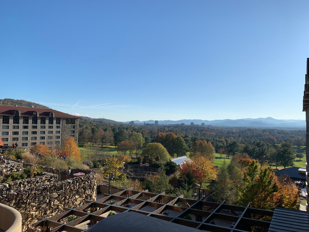 The view looking out at the Omni Grove Park Inn landscape. You can see a bar area directly below, small buildings, a green space, lots of trees, and a corner of a large stone hotel. In the distance you can see more trees and the mountains. The trees have green, red, orange, and yellow leaves.