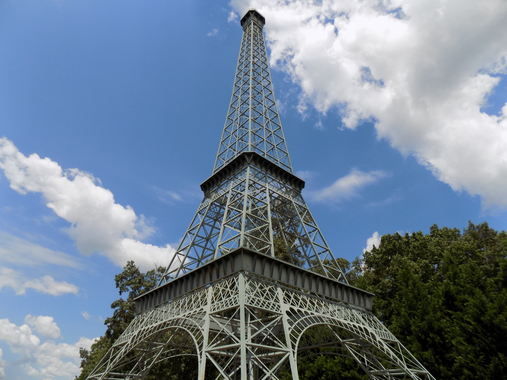 Looking up at a replica Eiffel Tower. It is a pale sage green. There are trees with green leaves behind part of it. The sky is blue and there are fluffy clouds.