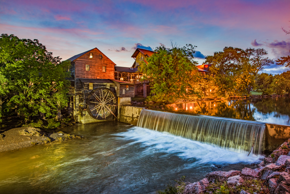 The old grist mill in Pigeon Forge, one of the best small towns in Tennessee. There is a large man made waterfall and trees and rocks surrounding the river. The sun is setting and the sky is purple and blue.