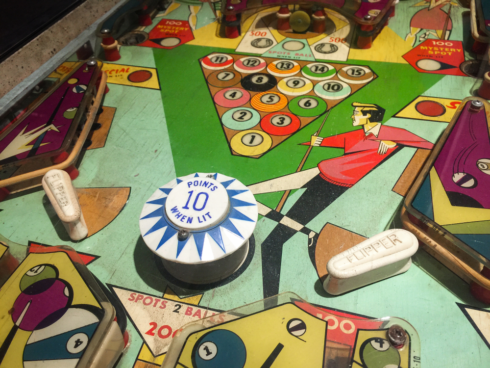 A close up image of an antique pinball machine. It has decorations that are themed around pool. There is a guy holding a pool stick, pool balls, and more.