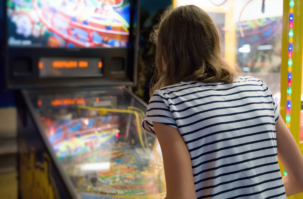A person with shoulder length hair wearing a striped shirt. They are bent over and playing a pinball machine.