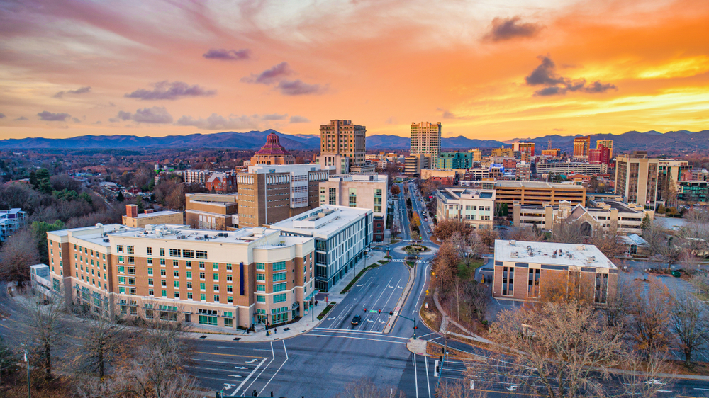 A city view of Asheville North Carolina city at sunset with mountains in the background and road leading to downtown