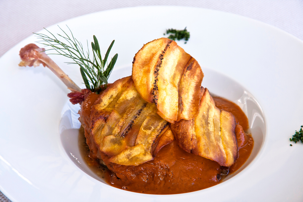 A upscale dish of Mexican pork with roasted plantains served in a red pepper glaze