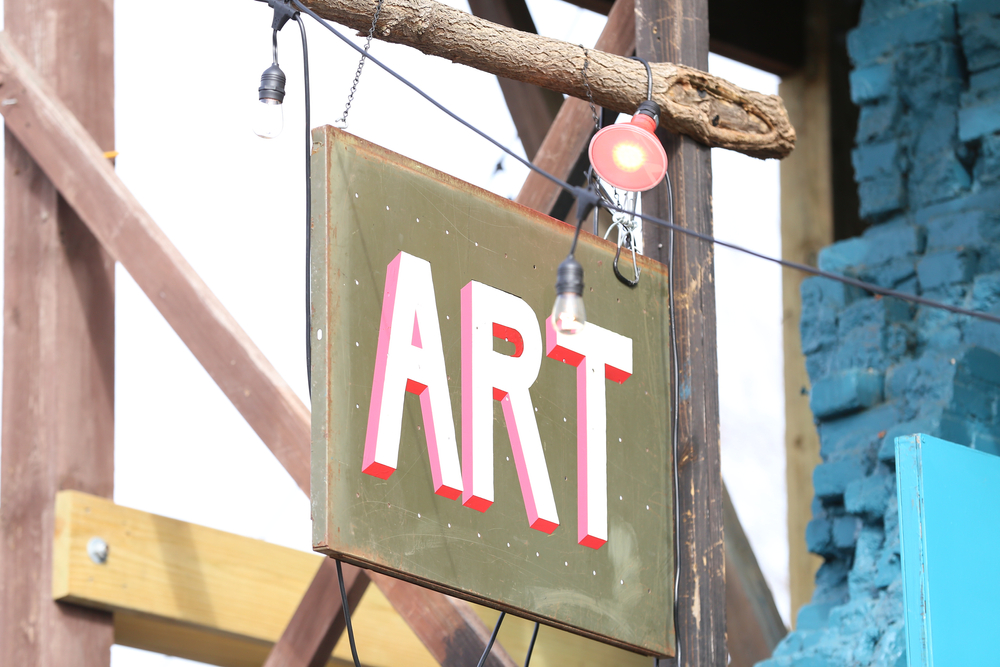 A sign on a wooden pole that reads 'ART' in block letters that are white, red, and pink. The sign is an army green color. You can see a string of lights near it and a brick building behind it.