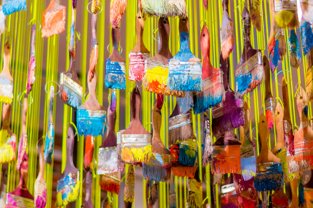 A close up of an art installation that is paintbrushes covered in various colors of paint hanging from yellow strings.