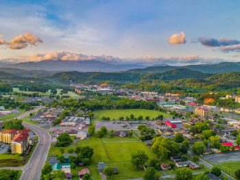 an aerial view of one of the cutest small towns in Tennessee. You can see grassy areas, small buildings, and mountains in the distance.