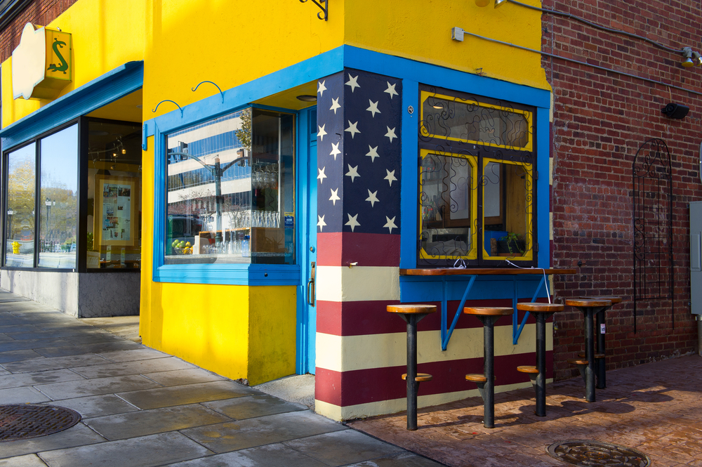 A building with the front painted bright yellow with blue trim. On the side there is an American flag painted on the building, the rest is brick. There is a counter at a window you can sit at and there are stools.