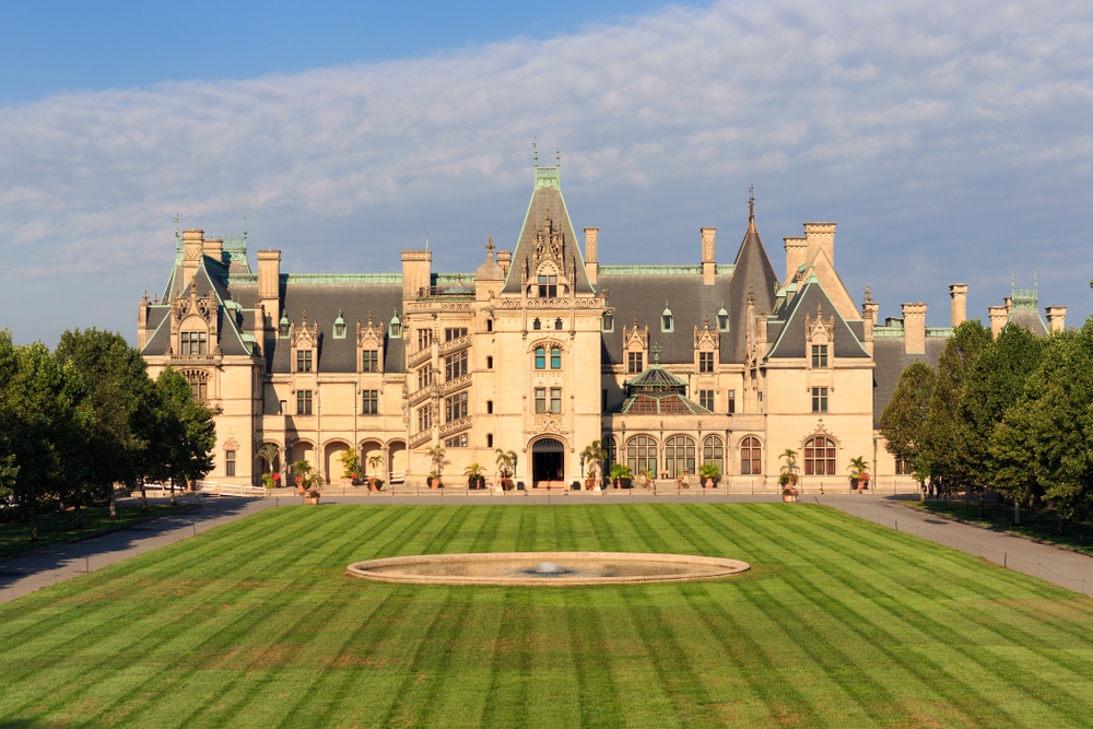 The front exterior of the Biltmore Estate. It is a large French-Gothic style house with tan walls, a grey roof, and blue green trim. In front of it is a large grassy area with a fountain in the middle. Around the grassy area and in front of the house is a paved walkway.