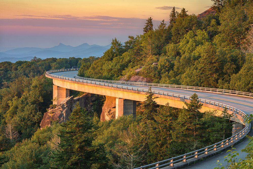 The Linn Cove Viaduct area of the Blue Ridge Parkway. It is a winding road that is lifted off of the rocky cliffside from supports underneath. The cliff next to it is covered in tall trees with green leaves. In the distance you can see other mountains silhouetted.