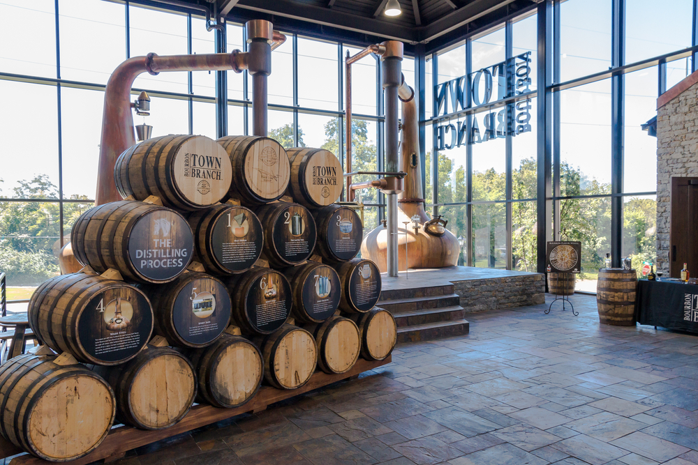entry way to distillery, large open windows and wooden barrels stacked into a pyramid