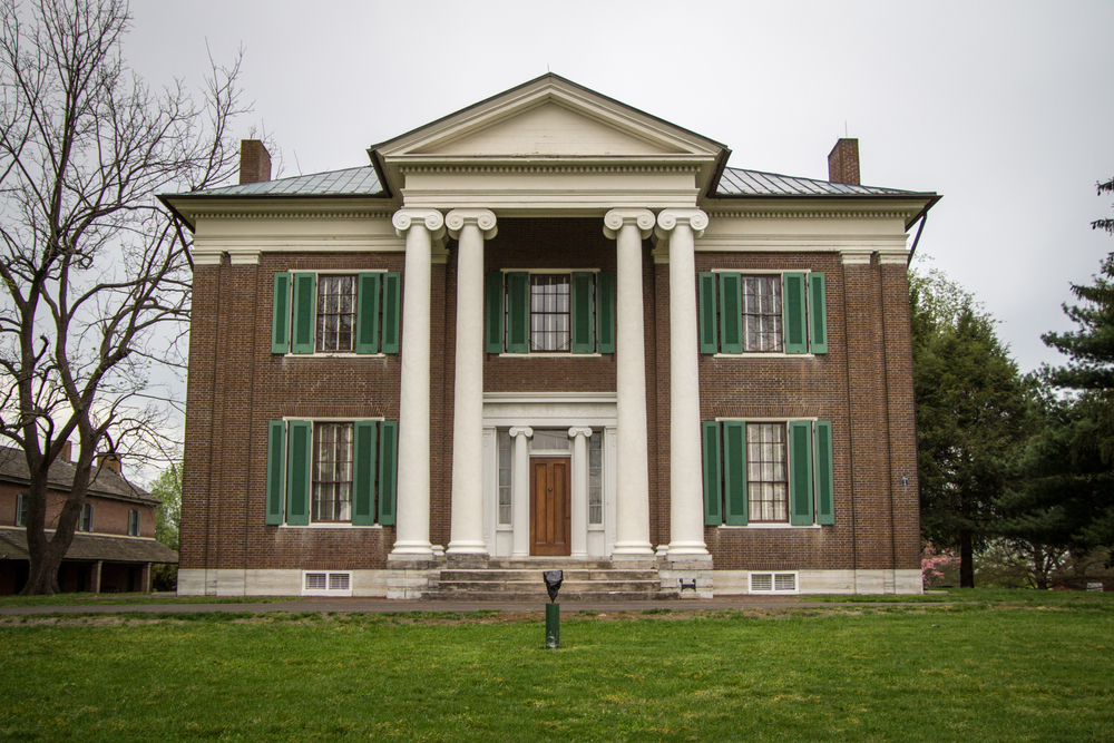 historic home with four columns in front of a green yard