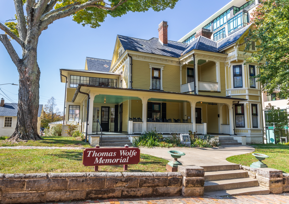 The exterior of a yellow Victorian house. It has a large front porch with rocking chairs on it, windows with black trim, and a small walkway leading to the front steps. There is a small lawn and a red sign that says 'Thomas Wolfe Memorial'.